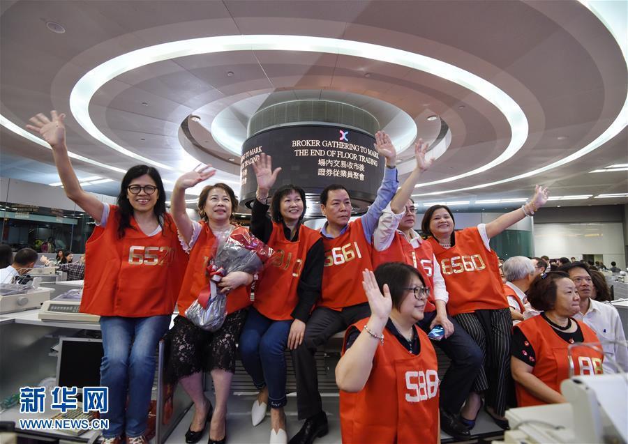 10月27日,在香港交易所交易大厅,身穿红马甲的交易员在挥手告别。随着香港交易所27日收市铃声响起,最后两位穿红马甲的交易员结束交易,准备收拾办公用品离开。自此,香港证券业在交易大堂内进行交易的时代画上圆满的句号。当日,香港交易所在交易大堂及展览馆举办了一场证券界人士聚会,数百名出市代表及嘉宾会聚一堂,共同回首了香港证券业的发展,在即将退出历史的交易大堂合影留念。新华社发(王申 摄)