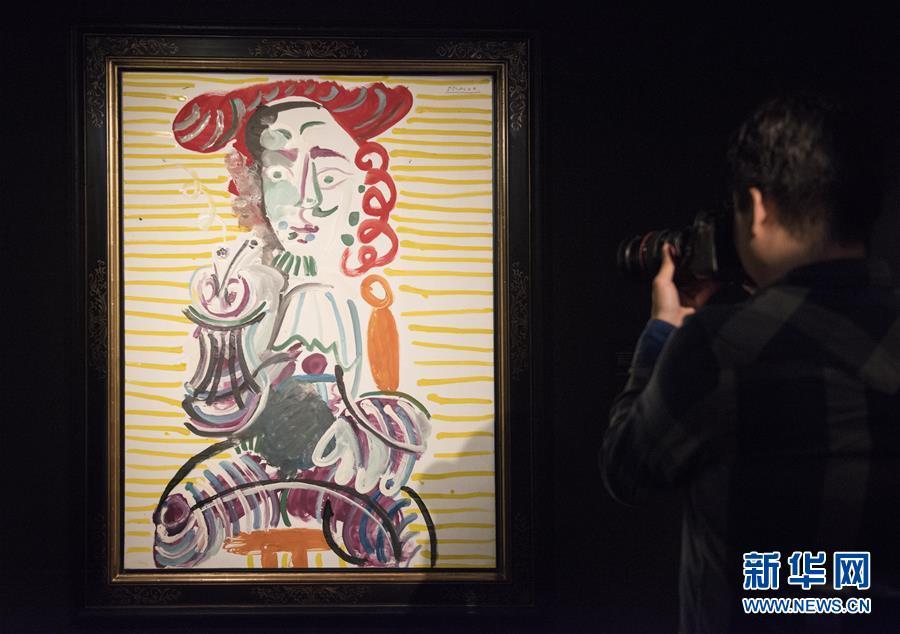 3月15日,在香港苏富比举行的媒体预展上,一名媒体工作人员在拍摄巴勃罗・毕加索的作品《拿烟斗的男子》。