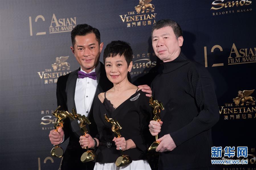 3月17日,古天乐、张艾嘉和冯小刚(从左至右)在后台展示奖杯。