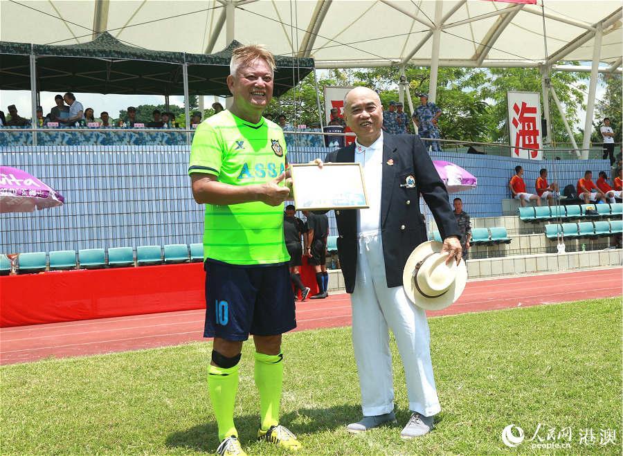 香港军民同乐委员会为香港明星足球队成员陈百祥送上证书。(摄影:辜雨晴)