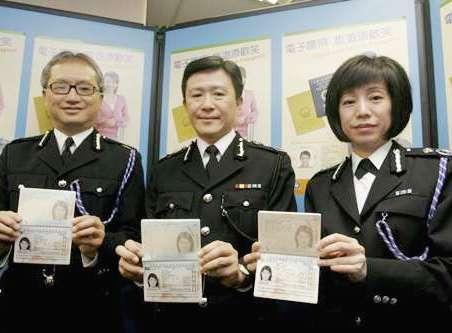 署理香港入境处处长白韫六(中)等展示电子护照