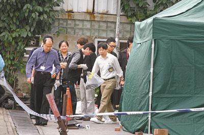 夫妇 现场 香港文汇报/鉴证科人员在夫妇堕楼现场检走一只拖鞋。图片来源:香港文汇报